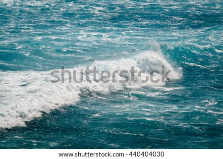 Close up view of beautiful blue ocean wave with white foam in Bali. Sun beam reflection on a deep blue wave surface. Close up view of a strong ocean wave. Surfer paradise spot in Bali with scenic wave - stock photo