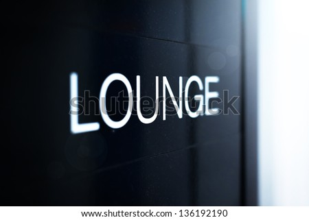 Close up view of black sign with big white inscription Lounge. Having rest or comfortable waiting of flight with good service at airport. Business trips and travelling. - stock photo