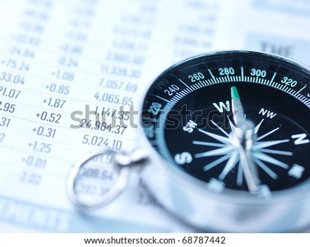 Close up view of blue compass and newspaper - stock photo
