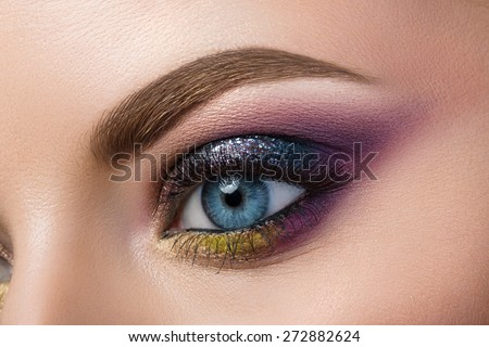 Close-up view of blue female eye with beautiful modern creative make-up - stock photo