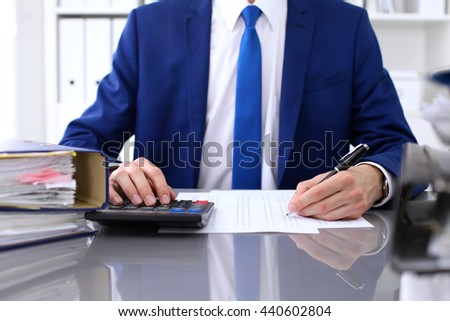 Close up view of bookkeeper or financial inspector hands making report, calculating or checking balance.  - stock photo