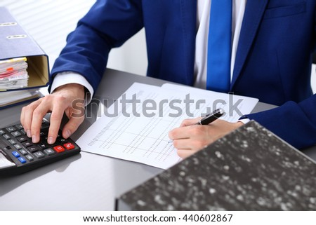 Close up view of bookkeeper or financial inspector hands making report, calculating or checking balance.