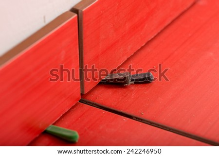 Close up view of bottom spacers used in tiling a wall to ensure an even gap for the grout between the tiles in a DIY and renovation concept. - stock photo