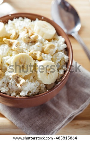 Close-up view of bowl with cottage cheese, banana and nuts