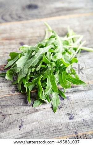 Close Up View Of Bunch Fresh Arugula Or Rucola Or Rocket Salad Leaves On Wooden Table