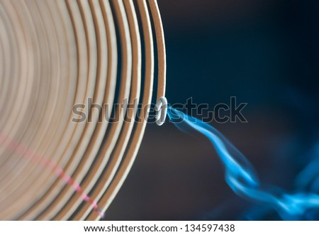 Close-up view of burning spiral incense stick with blue smoke going down on dark background. Traditional religious rituals in temple. Religion and traditions of East. Aroma and fragrance. - stock photo