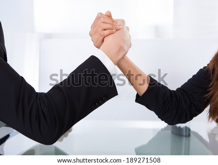Close-up view of business colleagues arm wrestling at desk in office - stock photo