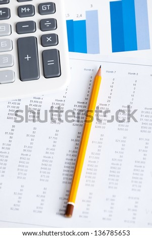 Close-up view of business stationery: calculator, pen, diagrams. Top view