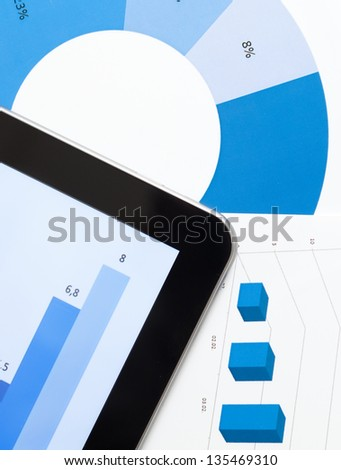 Close up view of business stationery: tablet and documents with diagrams