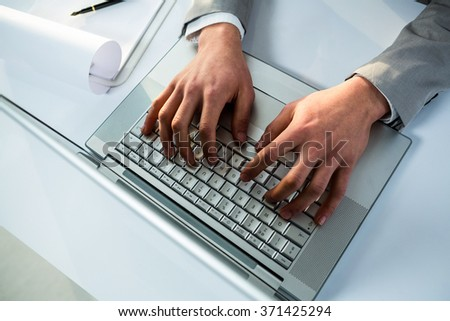 Close up view of businessman using laptop computer in office - stock photo
