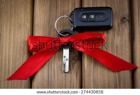 Close-up view of car keys with red bow as present on  wooden background - stock photo