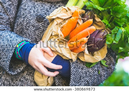 Close up view of carrots and some other vegetables held by a woman at market. They are fresh and natural, she is carrying them on some recycled paper bags, with strong concept of sustainability.