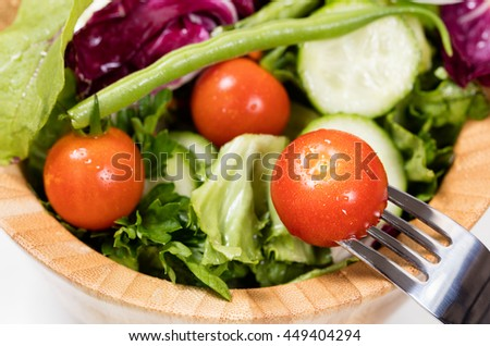 Close up view of cherry tomato and fork with bowl of salad in background. Selective focus on front tomato with fork