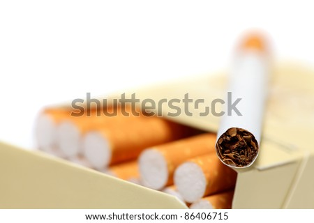 Close-up view of cigarette lying on pack isolated on white background - stock photo