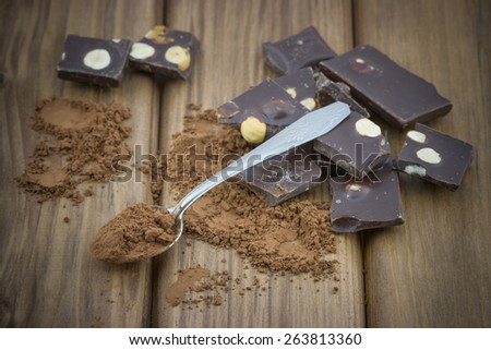 Close-up view of cocoa powder with spoon and broken dark chocolate bars with nuts on wooden background - stock photo