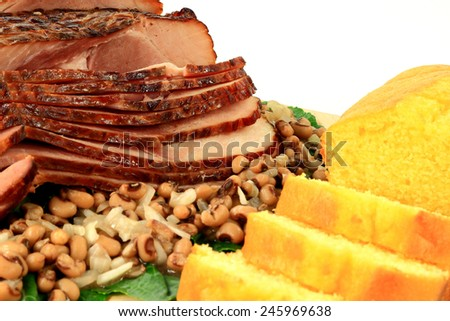 Close-up view of cooked Traditional for American South New Years Day Meal from cooked smoked Spiral-cut of Pork Ham, Black-eyed Peas, over Collard Greens and Corn Bread over white background  - stock photo