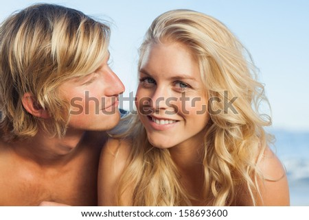 Close up view of couple lying while woman looking at camera on beach