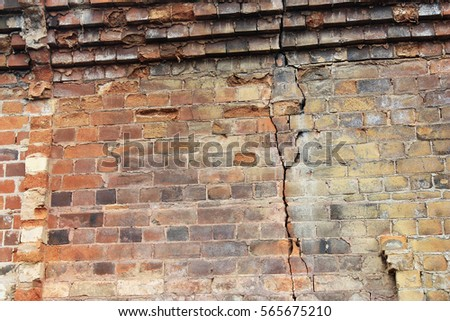 Close-up view of cracked old building brick wall with eroded bricks on top, background concept