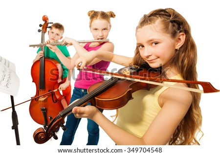 Close-up view of cute kids playing on musical instruments together on white background - stock photo