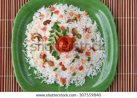Close up view of Delicious Indian Pulav or pilaf or fried rice,tomato flower on top in green plate. made of rice, vegetable, nuts, fruits or meat,chicken.Basmati or jasmine rice.Food art or decoration - stock photo