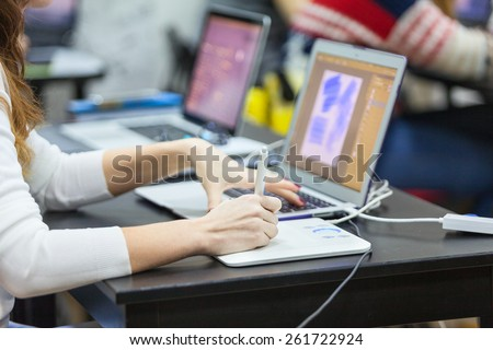 Close up view of designer hands drawing with graphic tablet with pen on white surface and working on laptop - stock photo