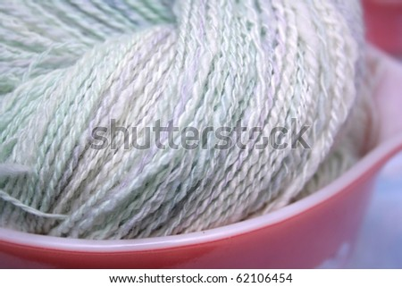 Close up view of details of light green with lavender and white 2 ply hand spun yarn made of hand dyed wool fiber displayed in a pink and white dish. - stock photo