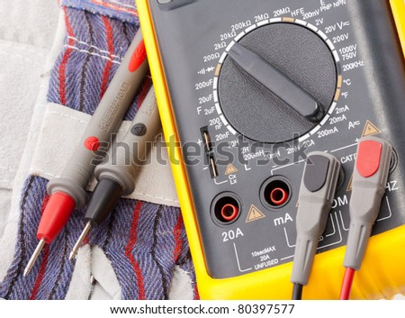 Close-up view of digital multimeter, probes and gloves - stock photo