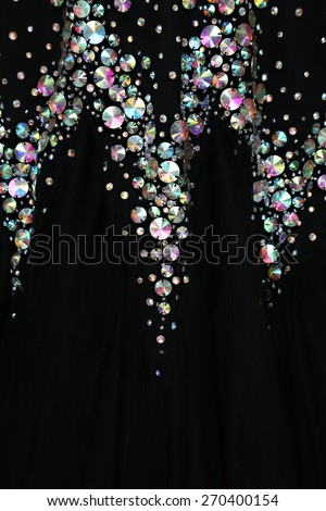 Close up view of elegant dress, Close up of a black dress covered with shiny rhinestones  - stock photo