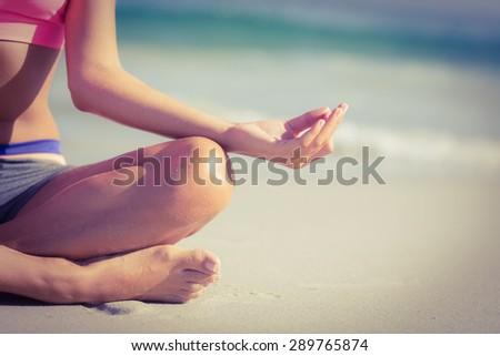 Close up view of fit woman doing yoga beside the sea at the beach - stock photo