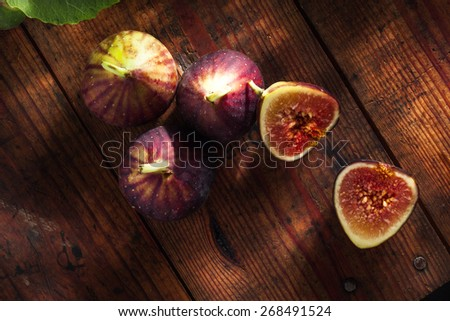 close up view of fresh figs and  leaf on color back - stock photo