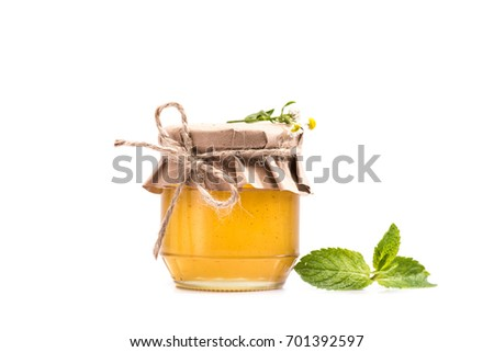 close-up view of fresh sweet honey in glass jar, mint leaves and chamomiles isolated on white