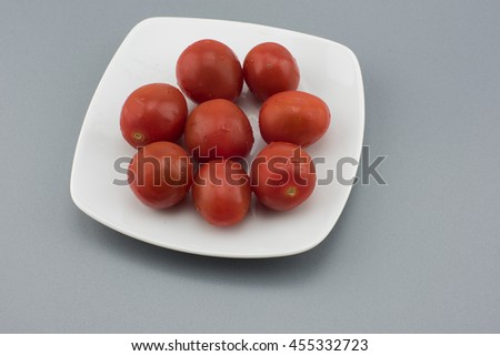 Close-up view of fresh tomatoes. Young juicy tomatoes. A lot of tomatoes. Fresh tomatoes. Fresh tomatoes on a white plate on dark background