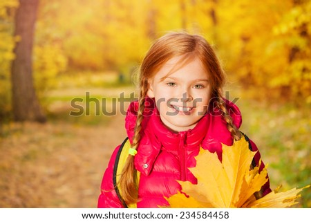 Close-up view of girl with rucksack and maple leaf - stock photo