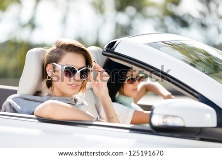 Close up view of girls wearing sunglasses in the automobile. Little holiday trip of friends