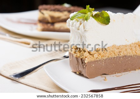 Close up View of Gourmet Slice of Tasty Three-Layered Cake with Leaves on Top of Whipped Cream, Served on White Plate at the Dining Table. - stock photo