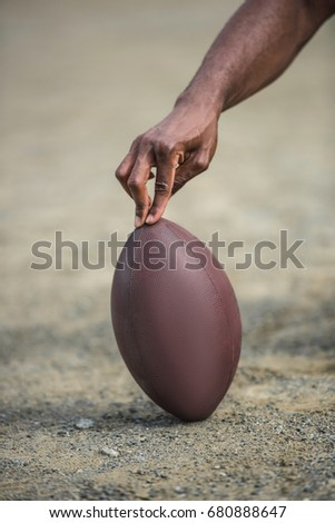 close-up view of hand holding american football ball