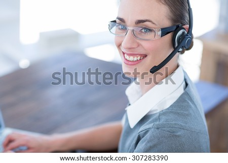 Close up view of happy businesswoman with headset in call center - stock photo