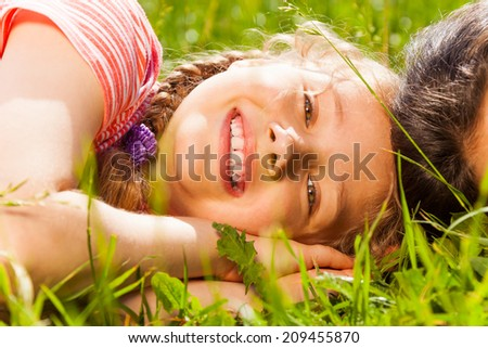 Close up view of happy girl laying on green grass