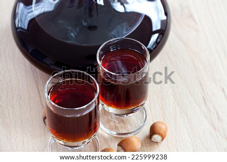 Close up view of homemade hazelnut liqueur in a glass carafe on a wooden background
