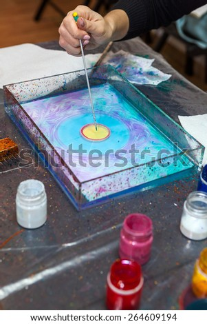 Close-up view of human hand making pattern with inks on water surface - stock photo