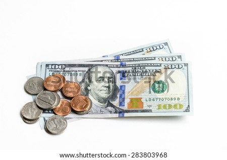 Close-up view of hundred dollars banknote and coins on white background