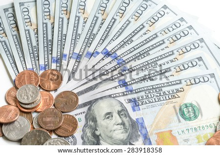 Close-up view of hundred dollars banknote and coins on white background - stock photo