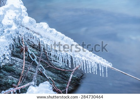 Close up view of ice, snow and frost on frozen rope and steel chain on water edge. Concept of cold, winter, frost, etc. Copy space available. - stock photo