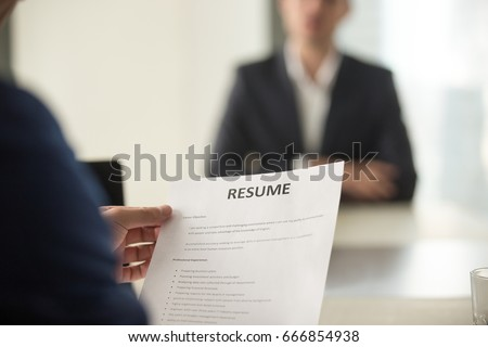Close up view of job interview in office, focus on resume writing tips, employer reviewing good cv of prepared skilled applicant, recruiter considering application, hr manager making hiring decision