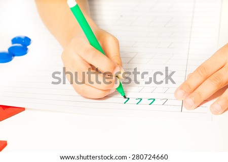Close-up view of kids hands writing letters - stock photo
