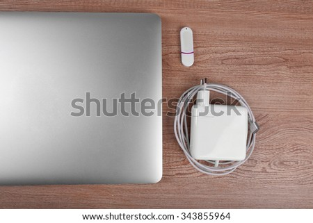 Close-up view of laptop and equipment at working place on brown wooden background - stock photo