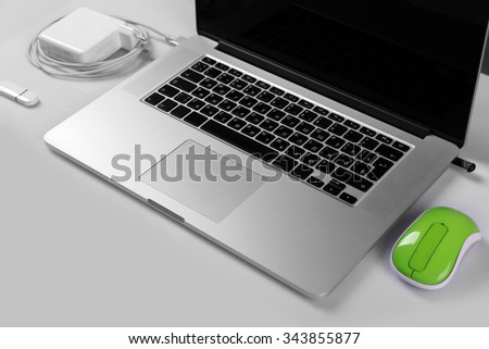 Close-up view of laptop and equipment at working place on silver glossy background