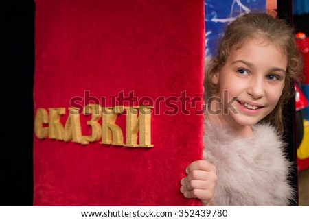 Close up view of little cute girl is standing behind red cover of Canterbury story. - stock photo