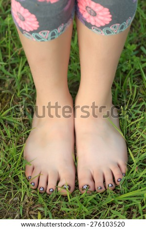 Close-up view of little shoeless girl toes on feet at green grass background - stock photo