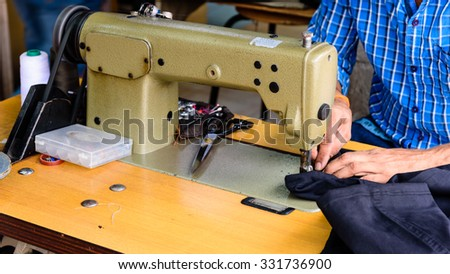 Close-up view of man hand with sewing machine in action. He is repairing a sewing black fabric on an old sewing machine. Panoramic style - stock photo
